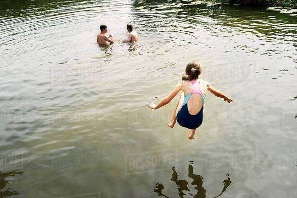 Rear view of girl jumping into lake Royalty-free stock photo