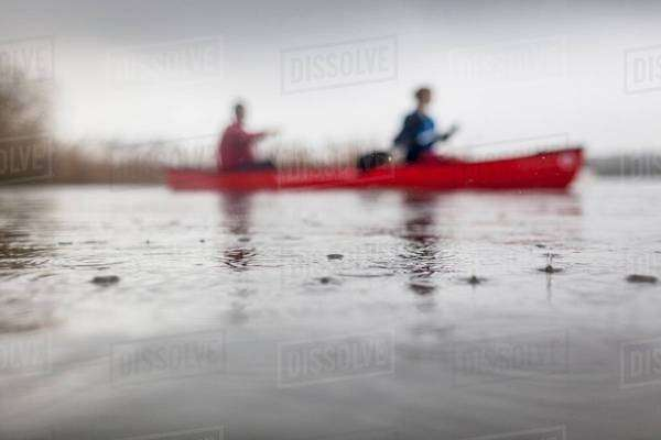 Two people canoeing in rain Royalty-free stock photo