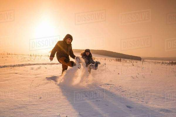 Man and son kicking snow powder at sunset, Sarsy village, Sverdlovsk Oblast, Russia Royalty-free stock photo