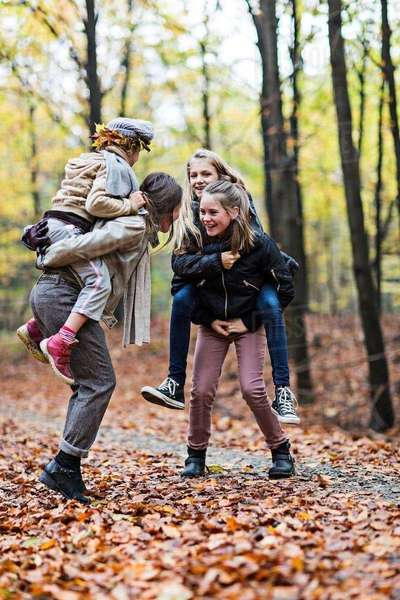 Mother and daughters playing piggyback ride in autumn forest Royalty-free stock photo