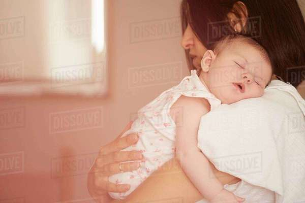 Mother carrying sleeping baby Royalty-free stock photo