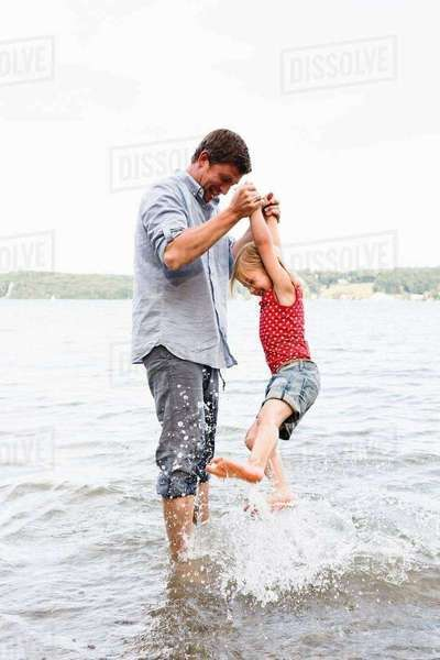 Mature man lifting up daughter from lake Starnberg, Bavaria, Germany Royalty-free stock photo