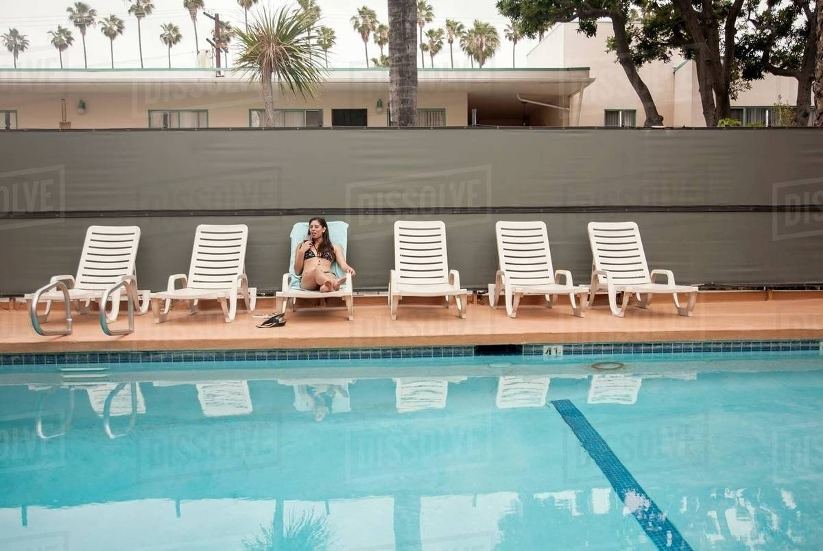 Young woman relaxing on deck chair beside swimming pool stock photo