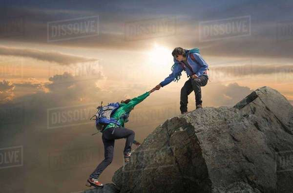 Climber helping partner reach mountain top, Mont Blanc, France Royalty-free stock photo