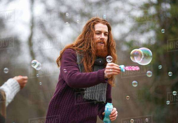Man blowing soap bubbles in countryside Royalty-free stock photo