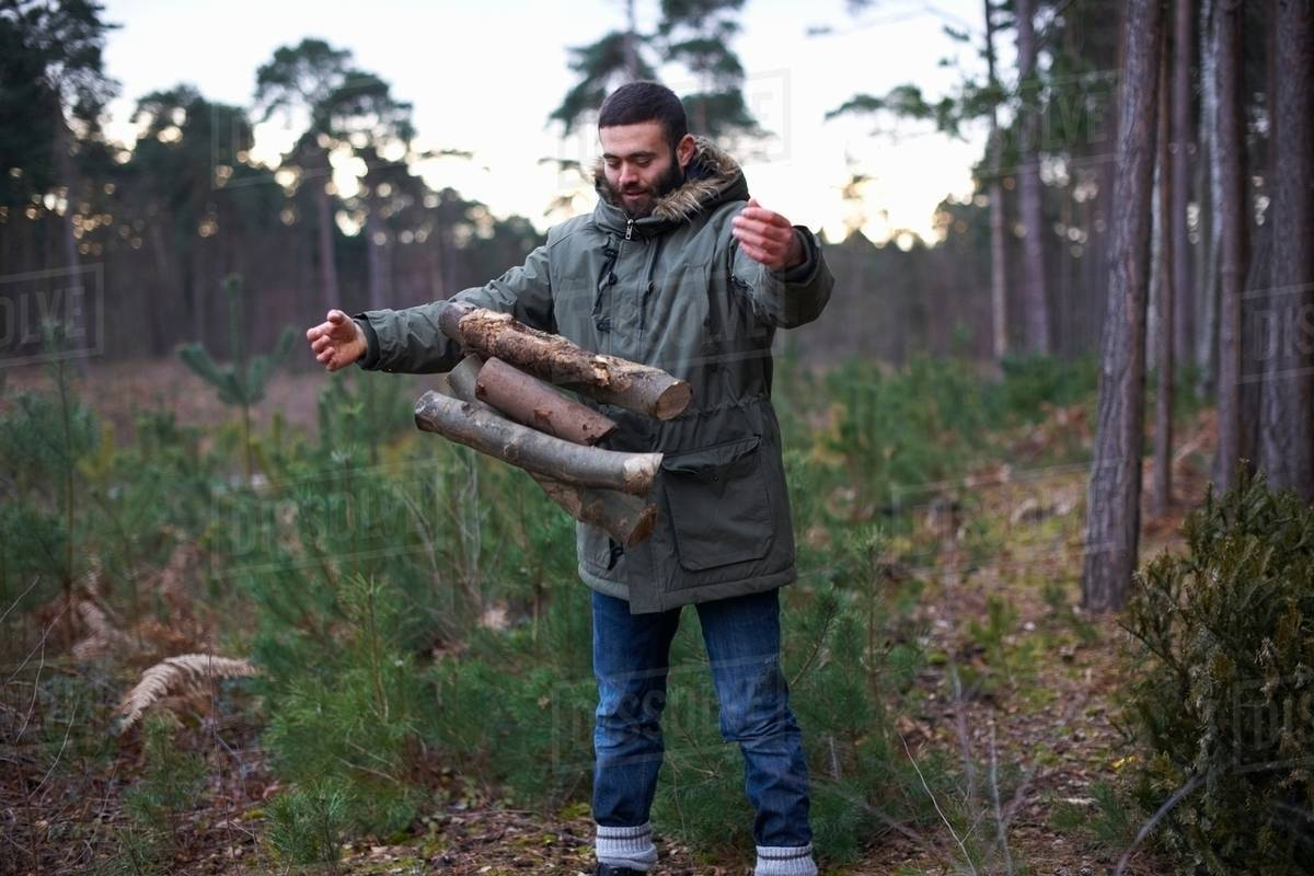 Young man dropping logs for campfire in forest Royalty-free stock photo