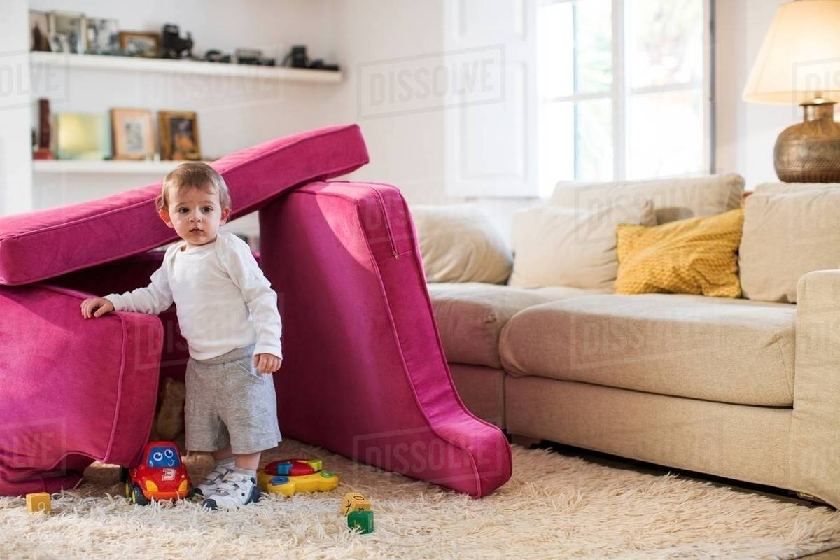 Baby Boy Playing In Fort Made From Sofa