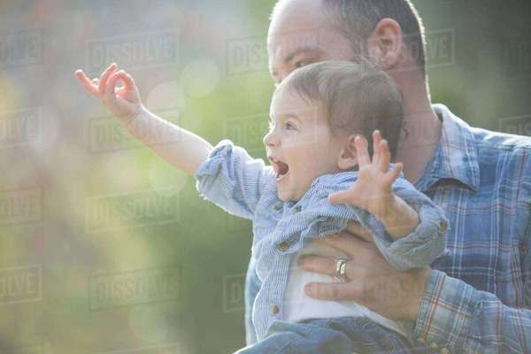 Side view of baby boy being held by father, pointing excitedly Royalty-free stock photo