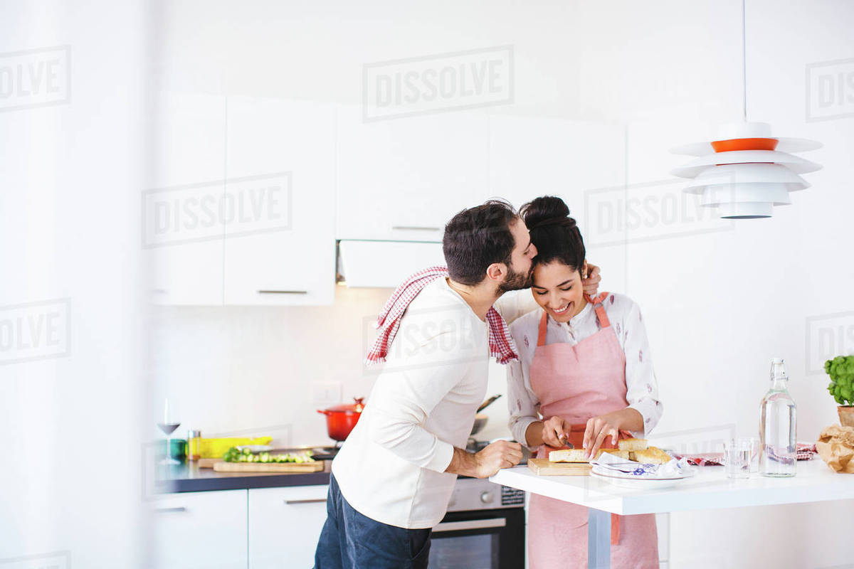 Romantic young couple in kitchen preparing food - Stock Photo - Dissolve