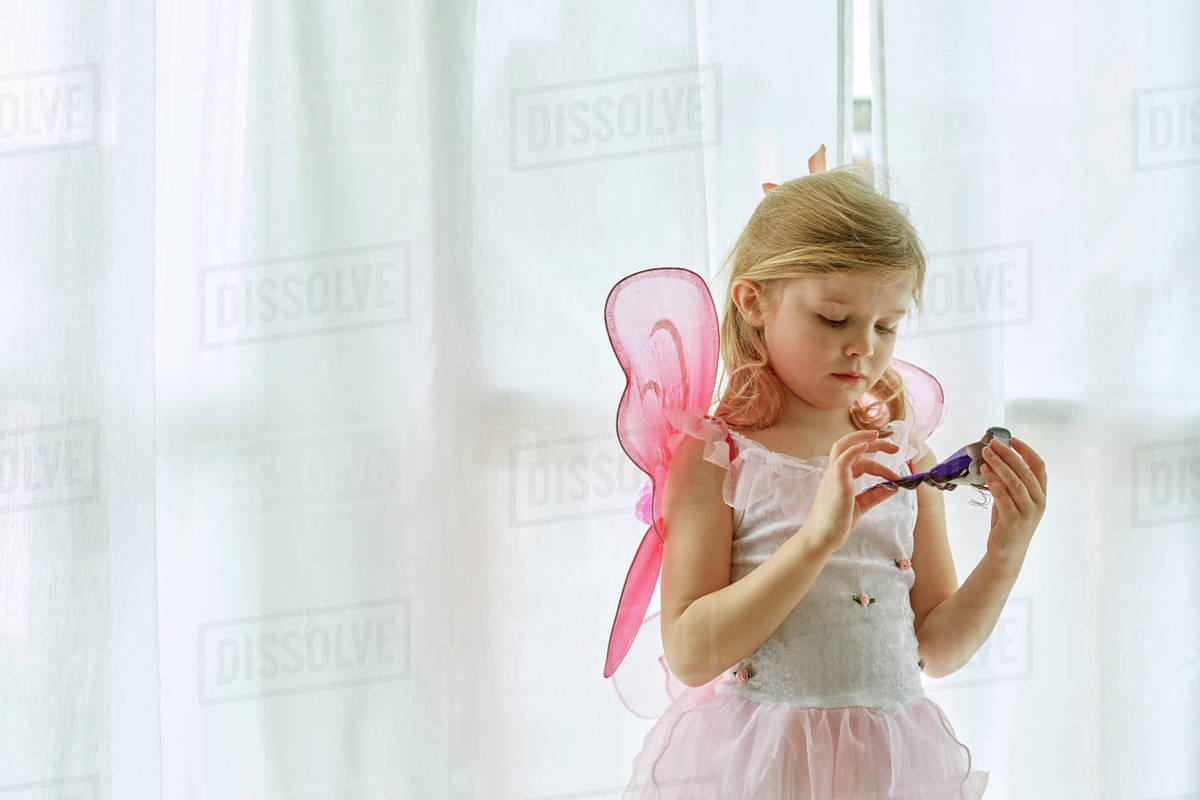 Girl in fairy costume playing by curtain Royalty-free stock photo