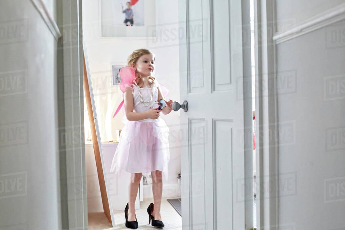 Girl in fairy costume and heels behind open door Royalty-free stock photo