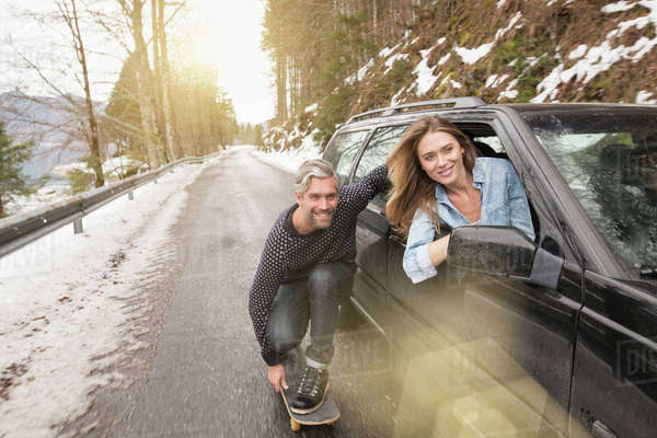 Mid adult man on skateboard, holding onto side of car, smiling Royalty-free stock photo