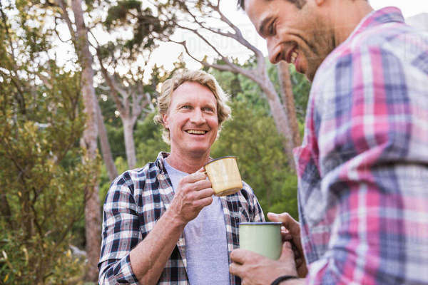 Two male hikers talking over coffee in forest, Deer Park, Cape Town, South Africa Royalty-free stock photo