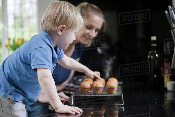 Mother and son waiting for freshly baked muffins to cool Royalty-free stock photo