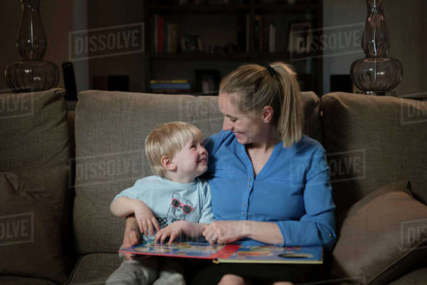 Mother and son sitting on sofa, reading book together Royalty-free stock photo