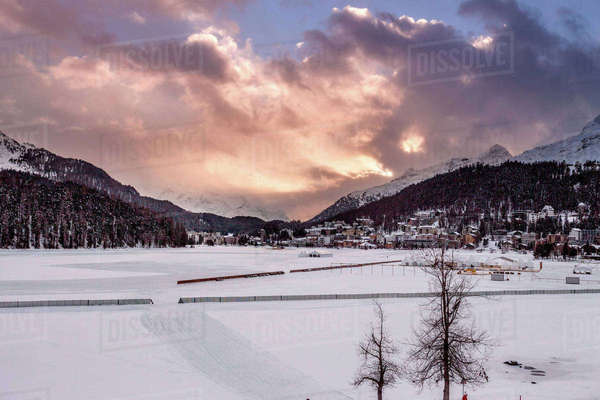 Village beneath mountain on snow covered landscape at sunset, Sankt Moritz, Switzerland Royalty-free stock photo