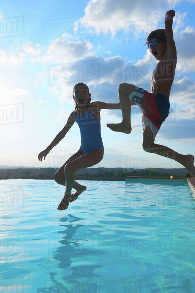 Girl and brother jumping into swimming pool, Buonconvento, Tuscany, Italy Royalty-free stock photo