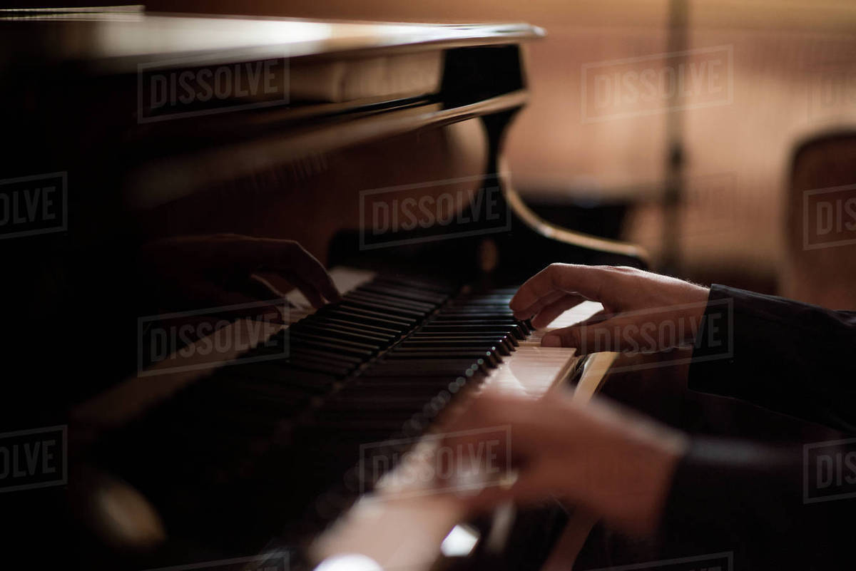 Hands of young man playing piano keys in bar at night stock photo