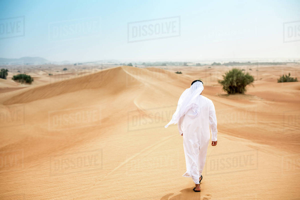 Rear view of middle eastern man wearing traditional clothes walking in  desert, Dubai, United Arab Emirates stock photo