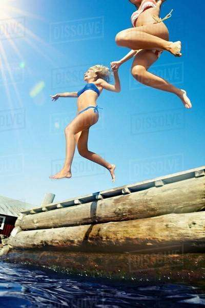 Teenage girls jumping into lake Royalty-free stock photo