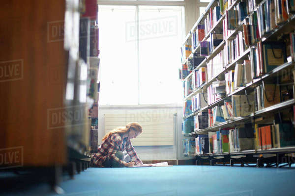Young female college student working on library floor Royalty-free stock photo