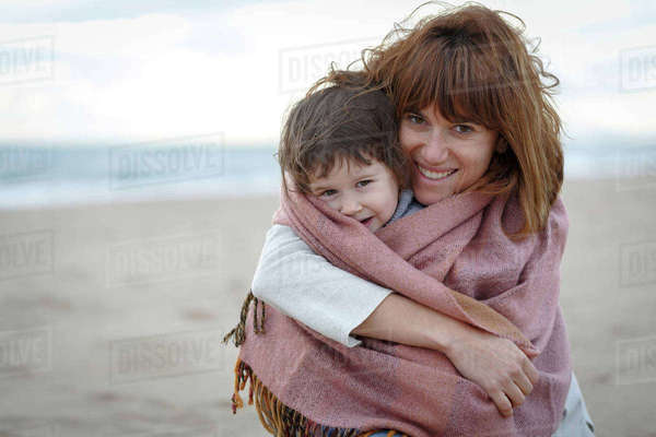 Mother and daughter wrapped in blanket hugging on beach Royalty-free stock photo