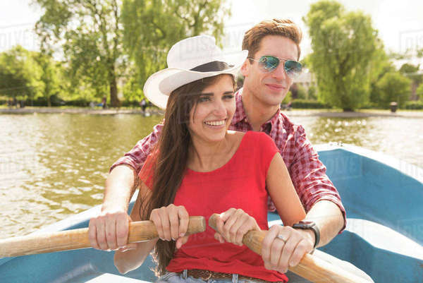 Happy young couple rowing a boat together in Regents Park, London, UK Royalty-free stock photo
