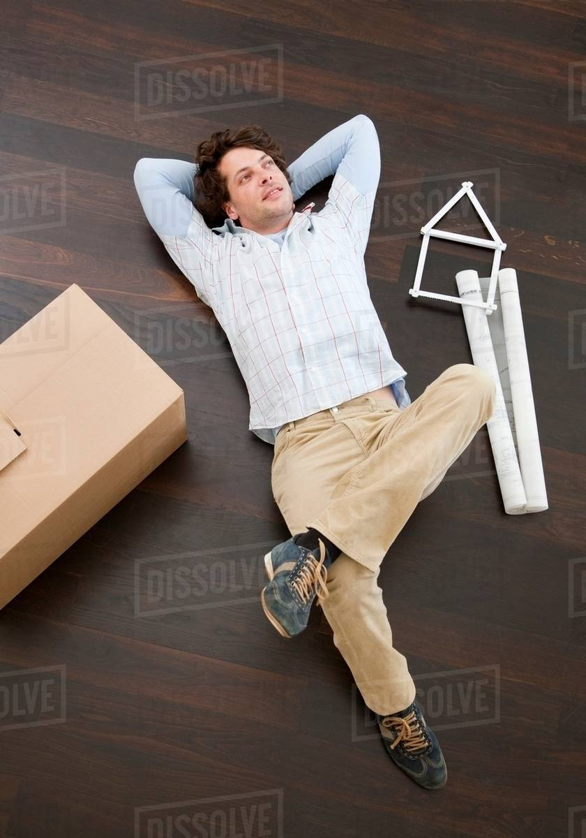 Man laying on floor with boxes - Stock