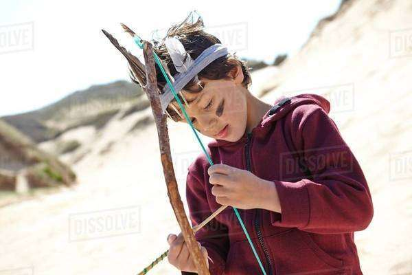 Young boy wearing fancy dress, holding home-made bow and arrow Royalty-free stock photo