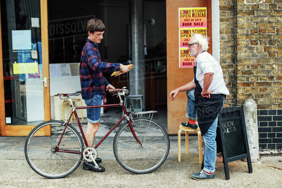 Young man with pushbike looking at post and standing with senior craftsman  outside print workshop stock photo