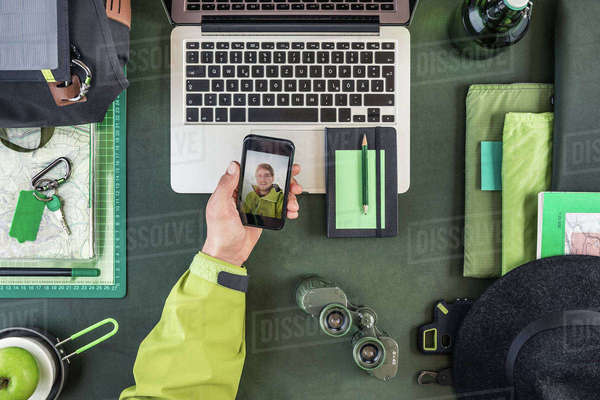 Overhead view of man's hand holding smartphone with hiking selfie Royalty-free stock photo