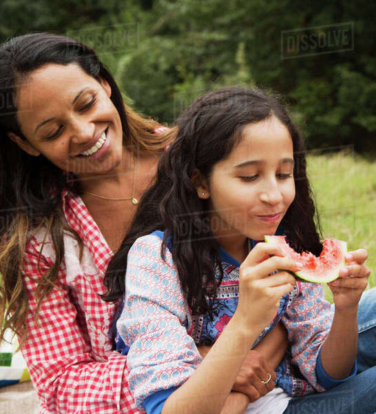 Mother and daughter sitting outdoors, daughter eating watermelon Royalty-free stock photo