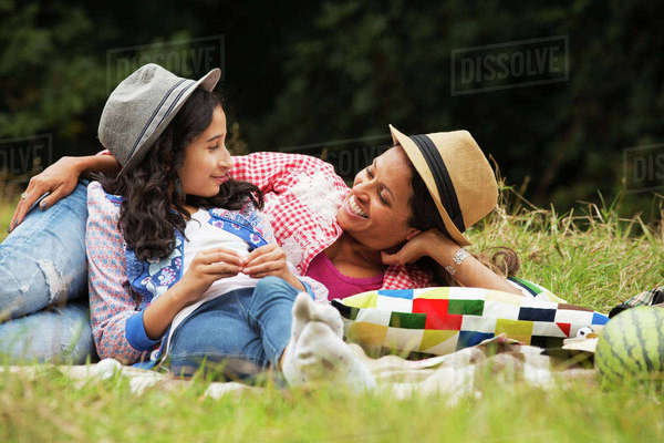 Mother and daughter relaxing outdoors, lying on picnic blanket Royalty-free stock photo