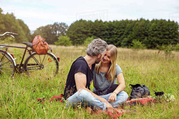 Romantic couple sitting on picnic blanket in rural field Royalty-free stock photo