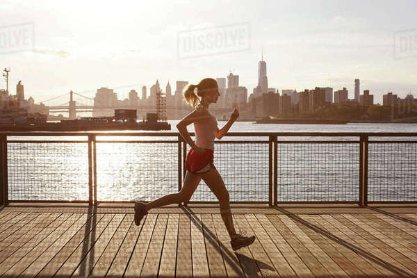 Side view of woman jogging on pier, Manhattan, New York, USA Royalty-free stock photo