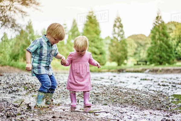 Brother and sister holding hands splashing in muddy puddle Royalty-free stock photo