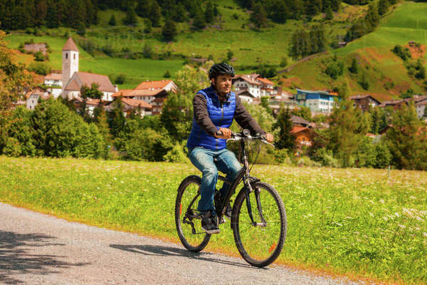 Mid adult man cycling on village path in Vinschgau Valley, South Tyrol, Italy Royalty-free stock photo