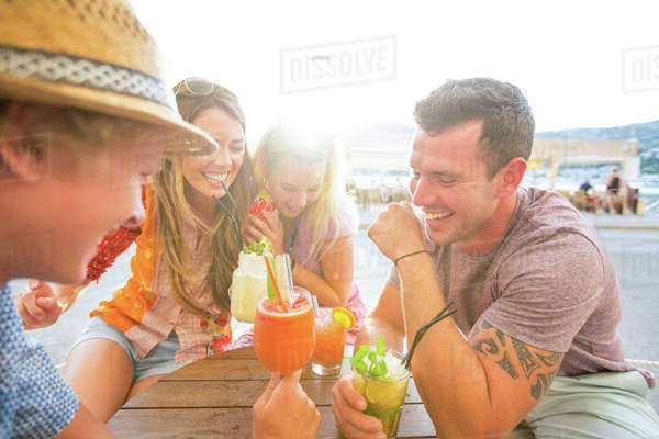 Two adult couples laughing over cocktails at waterfront restaurant, Majorca, Spain Royalty-free stock photo
