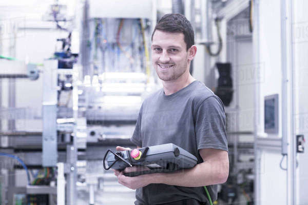 Portrait of engineer holding electronic control equipment in engineering plant Royalty-free stock photo