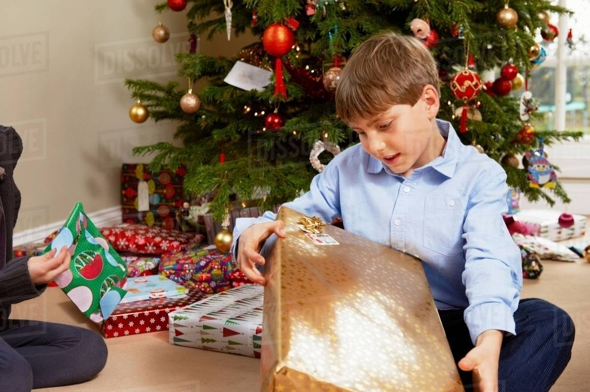 Children opening Christmas gifts - Stock Photo - Dissolve