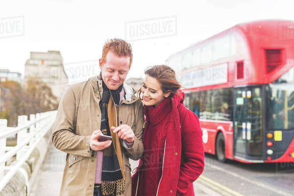 Couple using mobile phone on street, London, UK Royalty-free stock photo