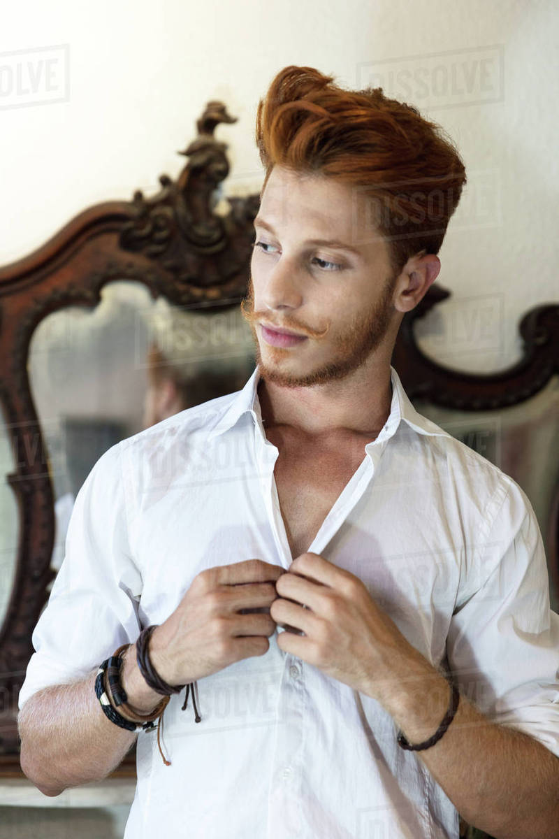 Young man with red hair, buttoning shirt D943_211_740