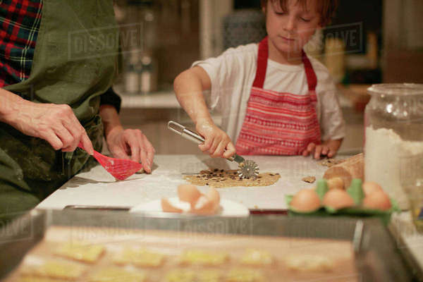 Cropped shot of woman and son cutting dough on kitchen counter Royalty-free stock photo