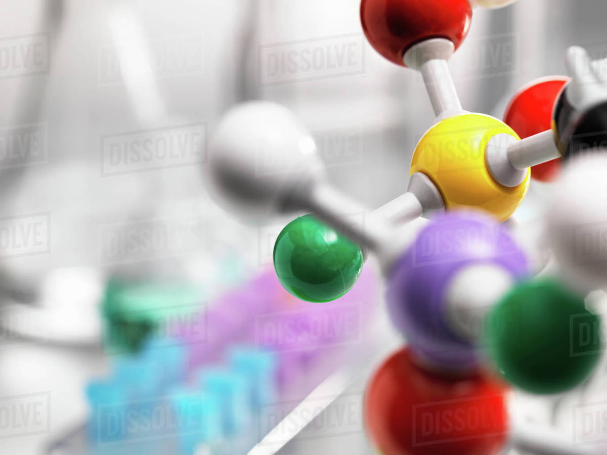 A molecular model of a chemical formula with laboratory equipment in the  background stock photo
