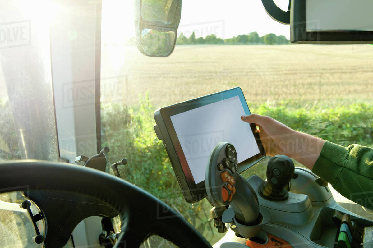 farmer s hand driving tractor using touchscreen on global