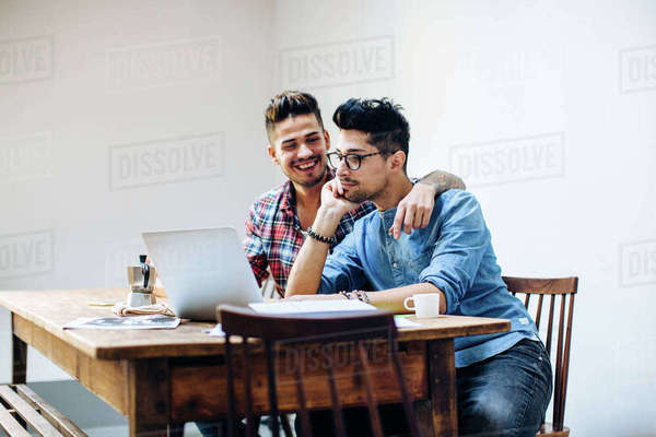 Male couple sitting at table, using laptop Royalty-free stock photo