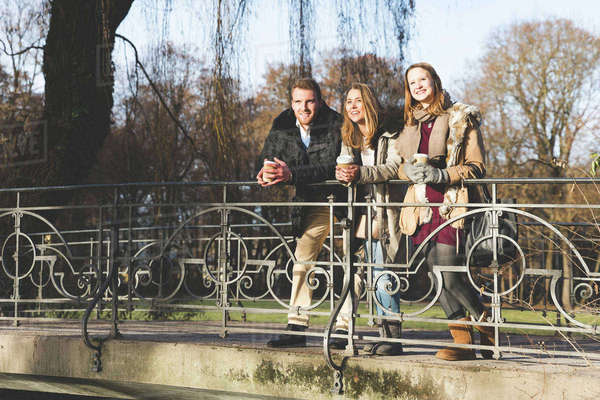 Young man and female friends looking out from park bridge Royalty-free stock photo