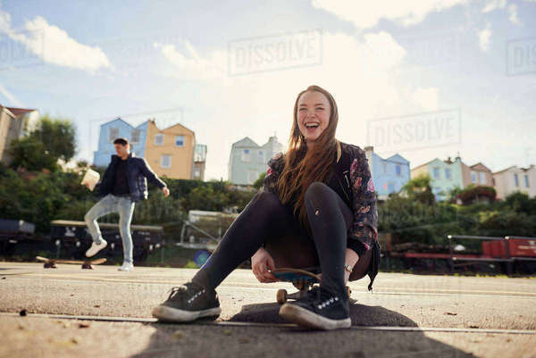 Two friends fooling around outdoors, young woman sitting on skateboard, laughing, Bristol, UK Royalty-free stock photo