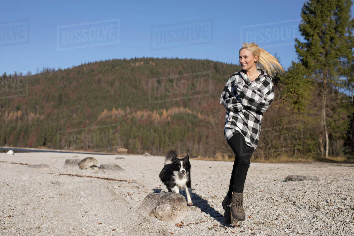 094ed22f8 Young woman running on lakeside with dog in Bavarian Alps - Stock ...