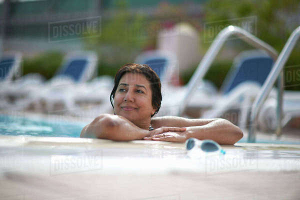 Mature woman leaning on swimming pool side, Dubai, United Arab Emirates Royalty-free stock photo